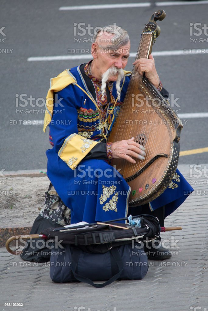 Elderly kobzar in a national costume plays a kobza on the street стоковое фото