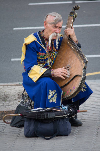 Cтоковое фото Elderly kobzar in a national costume plays a kobza on the street