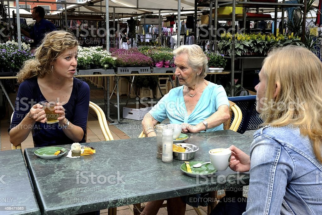 Elderly lady and young women on a terrace royalty-free stock photo
