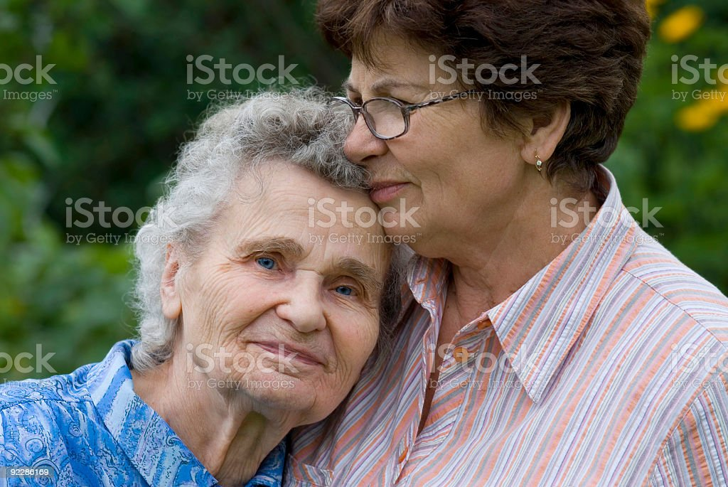 Elderly lady being held by another lady in the garden stock photo