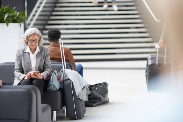 elderly lady browsing internet on smartphone - divano procrastinazione foto e immagini stock