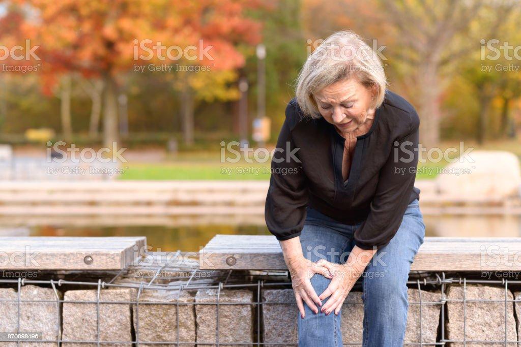 Elderly lady grabbing her knee in pain stock photo
