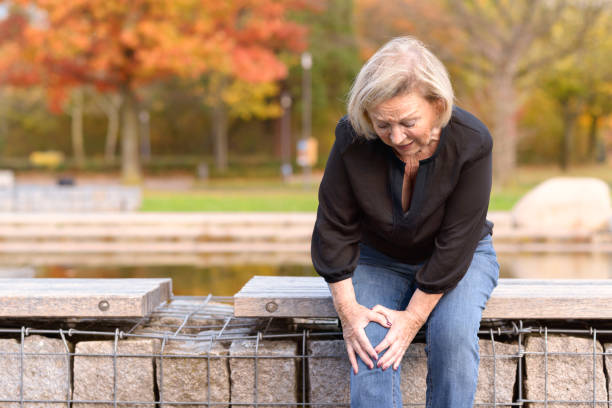 Elderly lady grabbing her knee in pain stock photo