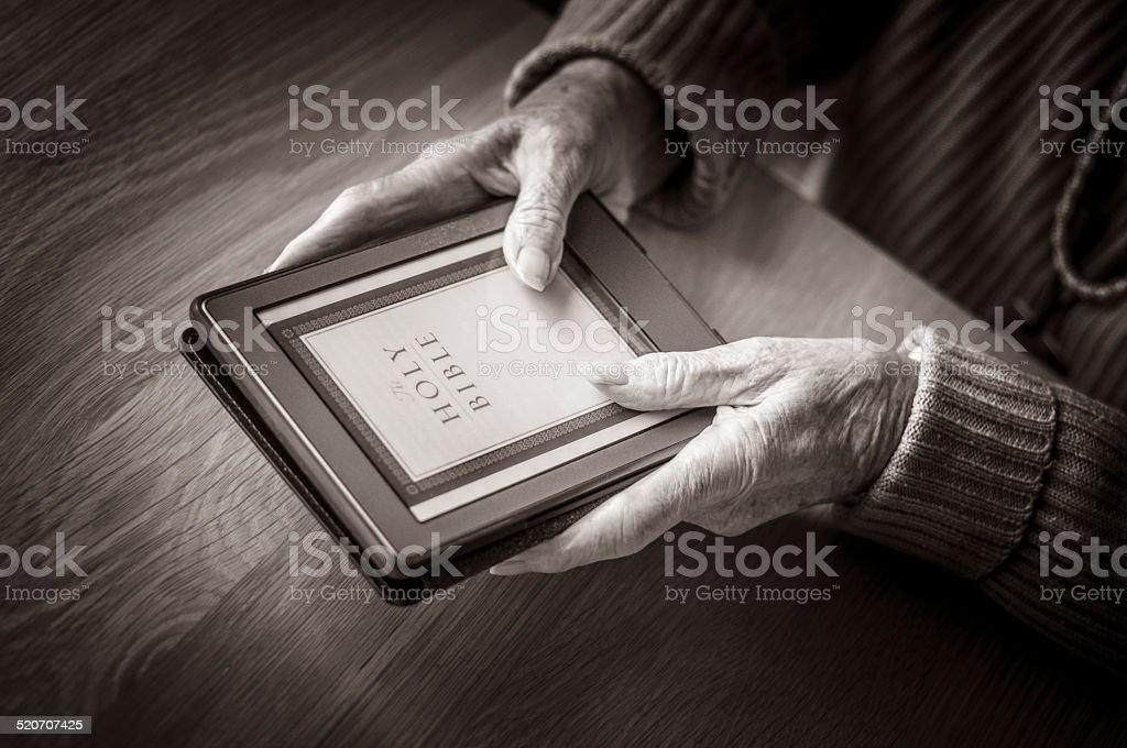 Elderly Lady Holding An E-Reader Viewing The Bible stock photo