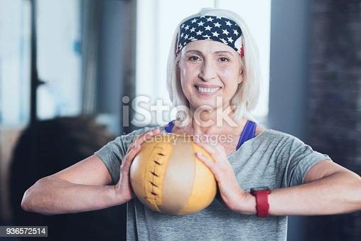 936573360istockphoto Elderly lady holding ball while training at gym 936572514