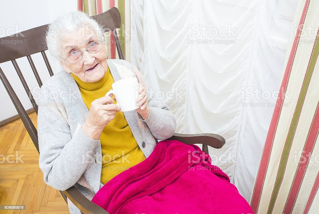 Elderly lady in chair stock photo