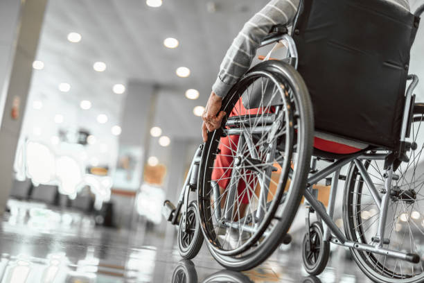 Elderly lady is using a wheelchair in airport stock photo