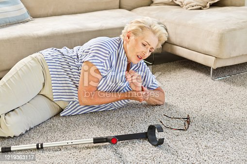 Tried and worried senior woman lying on the carpet in the living room and holding her wrist. Elderly lady falling down at home. Crutches on the floor.