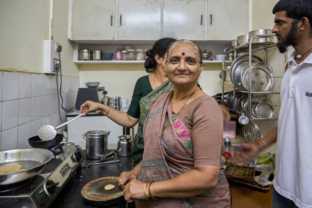 Elderly Lady preparing puri and Daouterinlay fring grand sun waching mumbai