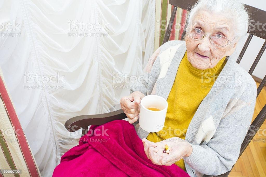 Elderly lady taking medication stock photo