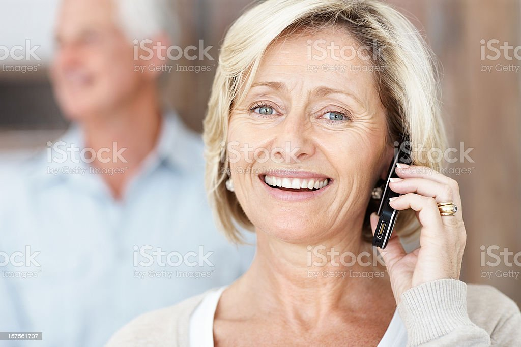 Elderly lady talking on cellphone with man in the background royalty-free stock photo