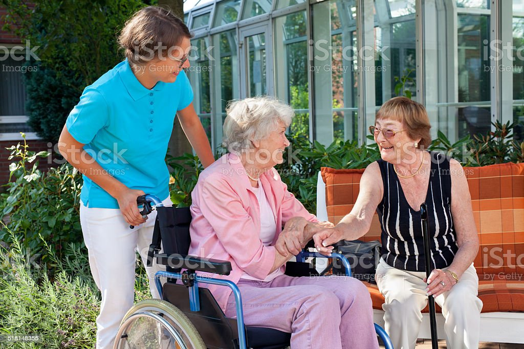 Elderly lady with a carer talking to friend. stock photo
