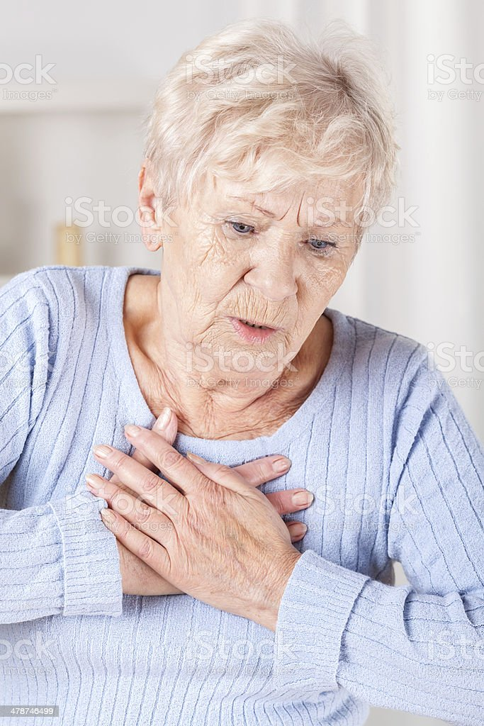 Elderly lady with chest pain stock photo