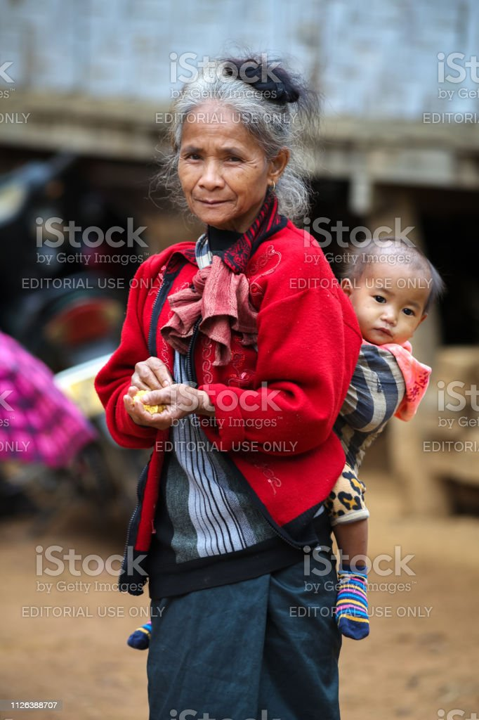 Nong Khiaw, Laos - December 12, 2018: Elderly Lao (laotian) minority woman is standing with a baby on her back in a mountain village near Nong Khiaw - a city in northern Laos stock photo