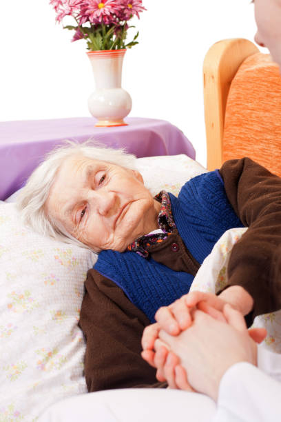 Elderly lonely woman rests in the bed stock photo