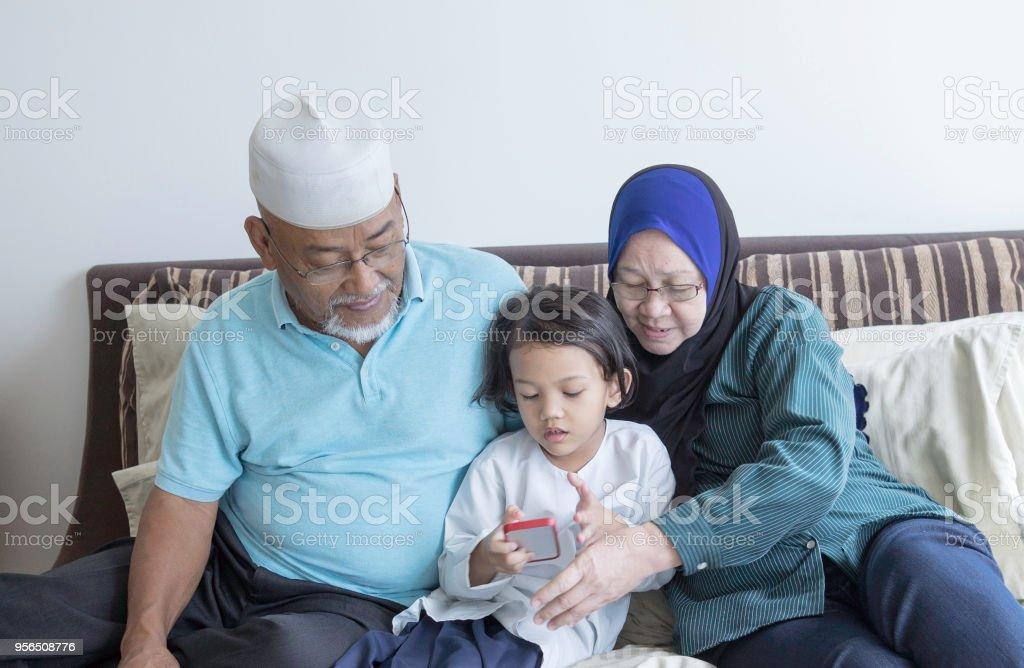Ältere Malay Paar mit einem Kind überprüft ihr Telefon - Lizenzfrei Alt Stock-Foto