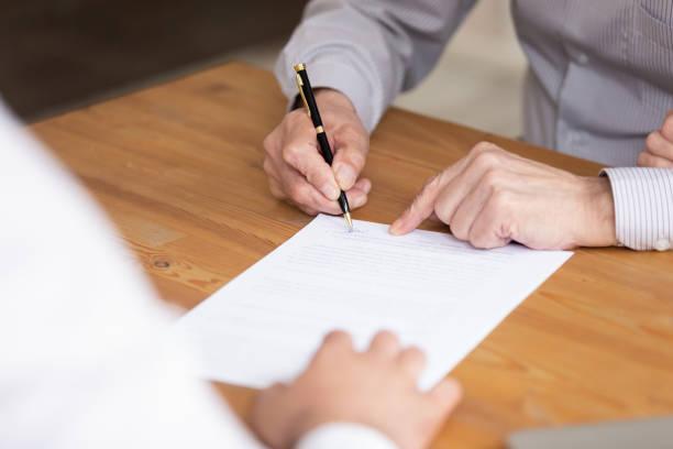 Documento de firma de mano masculino de edad avanzada de cerca imagen - foto de stock