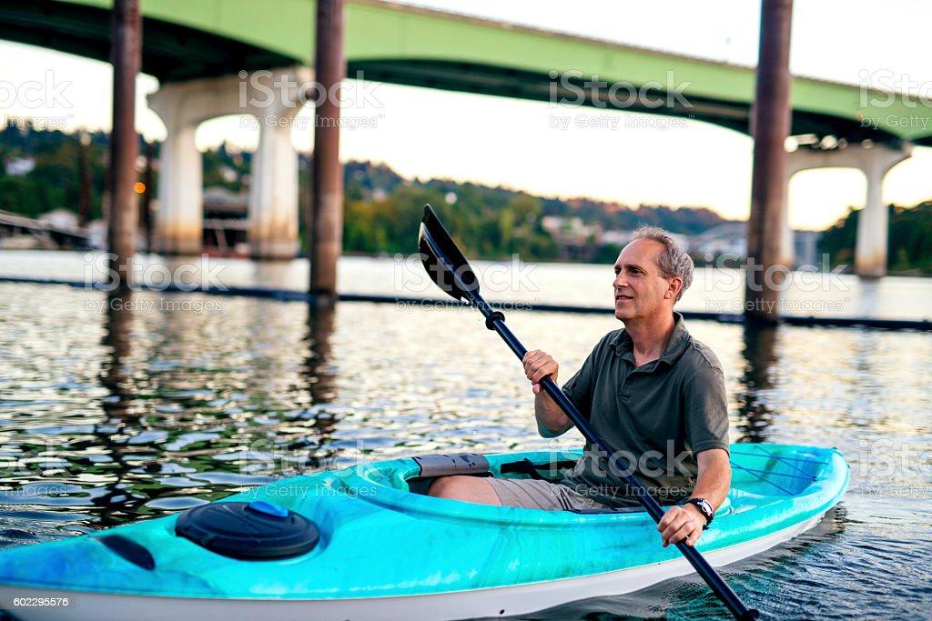 Elderly male kayaking in a single person kayak stock photo