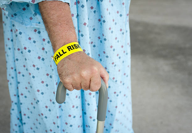 Elderly Man A Fall Risk An elderly man wearing a fall risk bracelet around his wrist at the hospital. Wearing a blue gown and walking with a cane. wristband stock pictures, royalty-free photos & images
