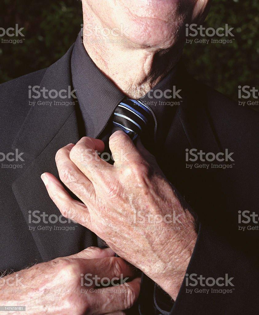 Elderly man adjusting tie, close-up royalty-free stock photo