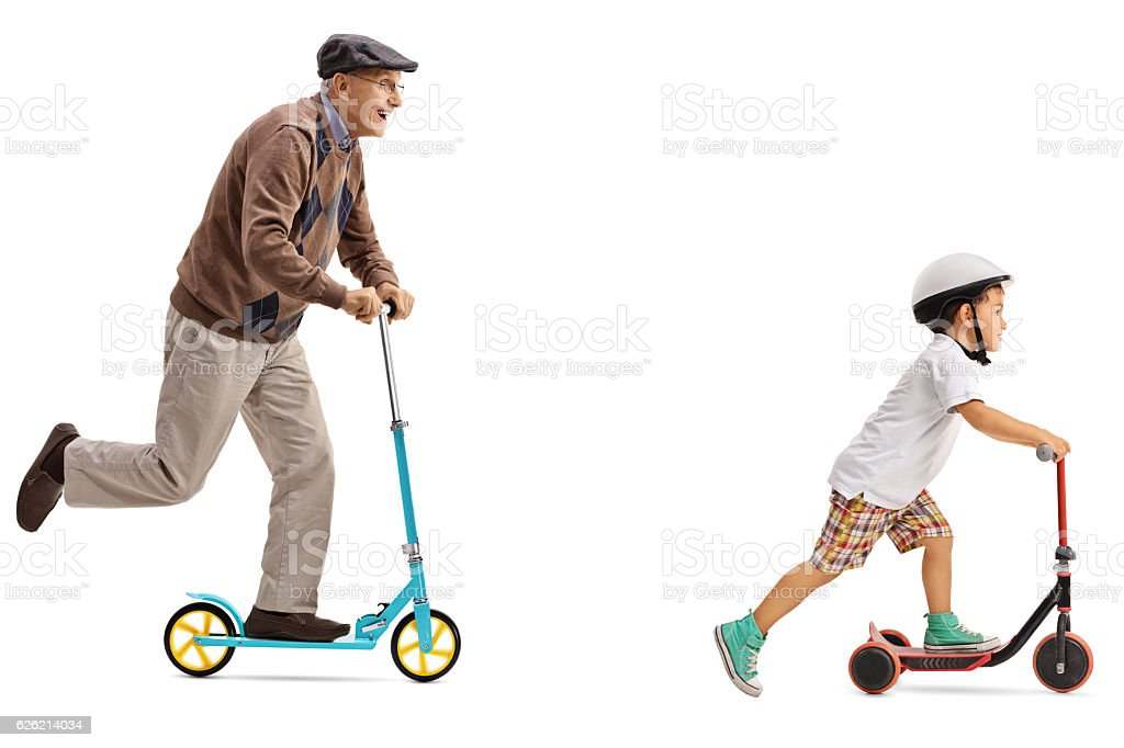 Elderly man and a little boy riding scooters stock photo