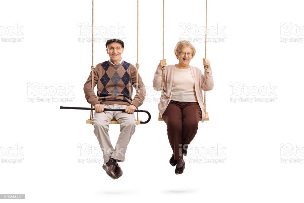 Elderly man and an elderly woman sitting on swings stock photo
