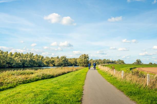 Elderly man and woman cycling on a bike path at the top of a dike at picture id1047461168?b=1&k=6&m=1047461168&s=612x612&w=0&h=y0tf7ej6ac24l6skm3uy 5plya72bg1t7b51v9dkijs=