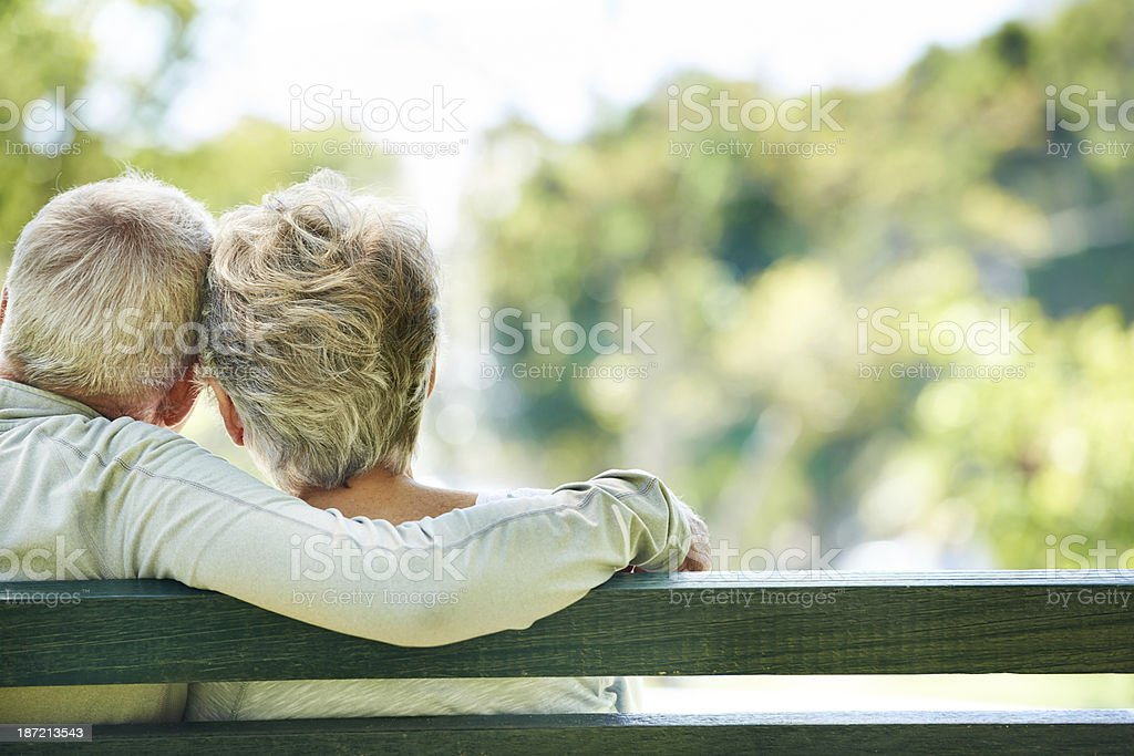 Elderly man and woman embracing on outdoor bench stock photo