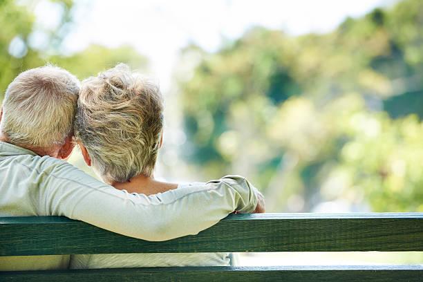 Vieil homme et femme embrassant sur un banc en plein - Photo