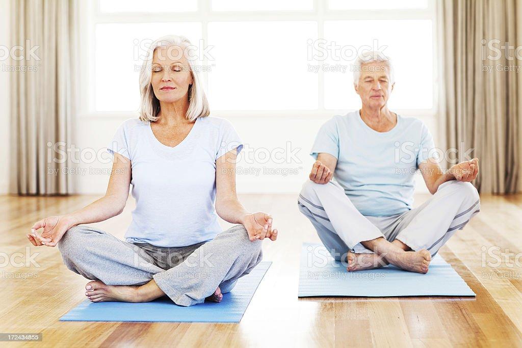 Elderly man and woman meditating stock photo
