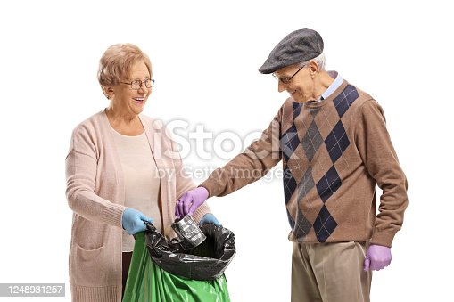 Elderly man and woman putting a waste can in a in a plastic garbage bag isolated on white background