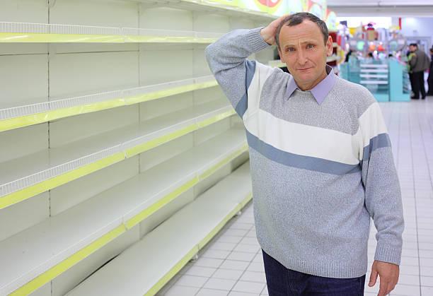 Elderly man at empty shelves in shop stock photo