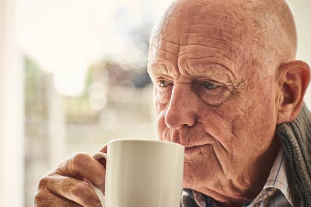älterer mann zu hause trinken kaffee - gesichtertassen stock-fotos und bilder