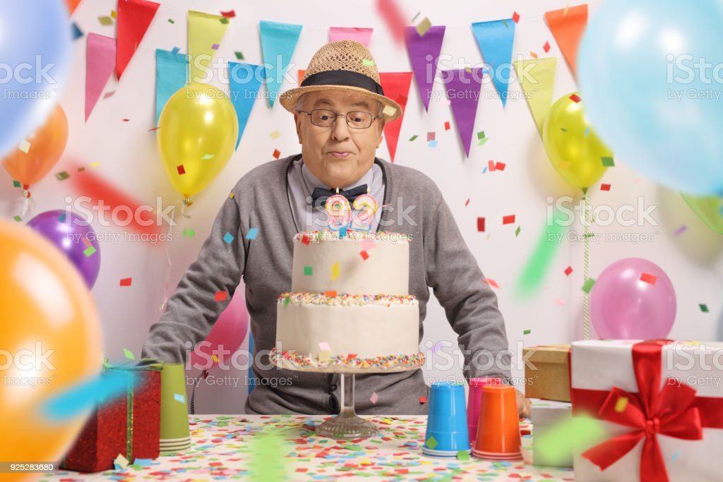 Elderly man blowing candles on a birthday cake with confetti...