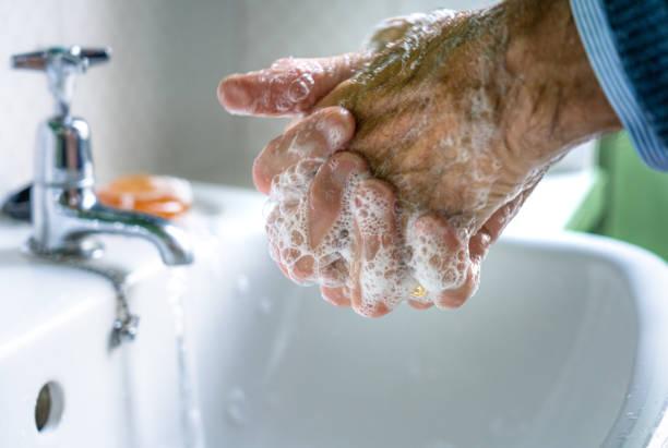Elderly man carefully washing his hands stock photo