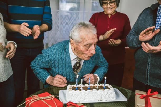 älterer mann feiert geburtstag mit familie - super torte stock-fotos und bilder