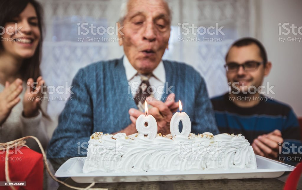 Grandfather celebrates 90th birthday , blows candles surrounded with...