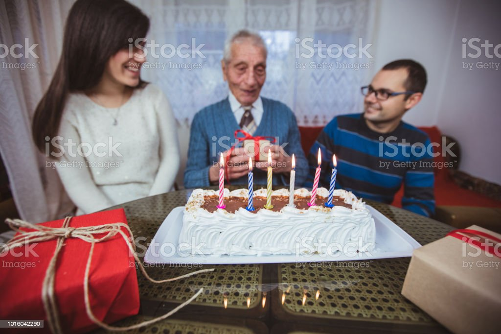 Grandfather receiving birthday gifts from family
