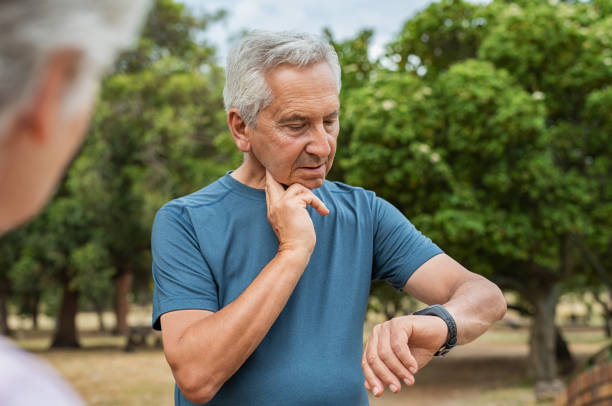 elderly man checking pulse after running - taking pulse stock photos and pictures