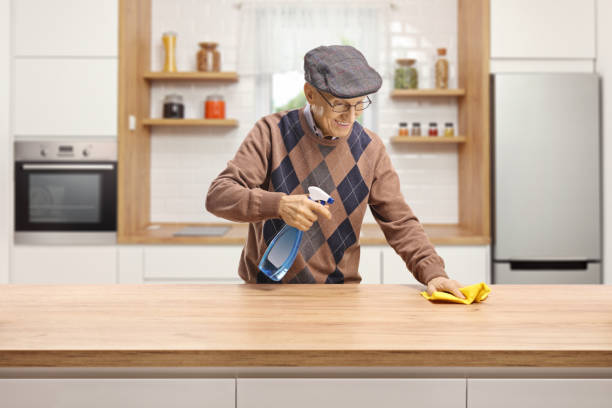 ältere mann putzen eine holztheke in einer küche - backofenfenster reinigen stock-fotos und bilder