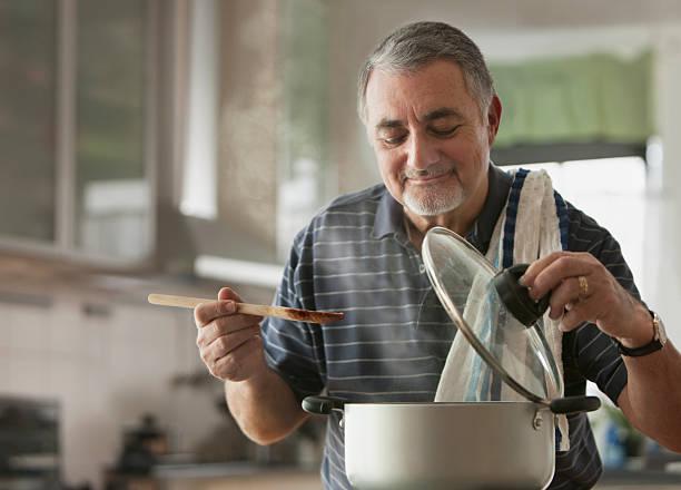älterer mann kochen - einzelner senior stock-fotos und bilder
