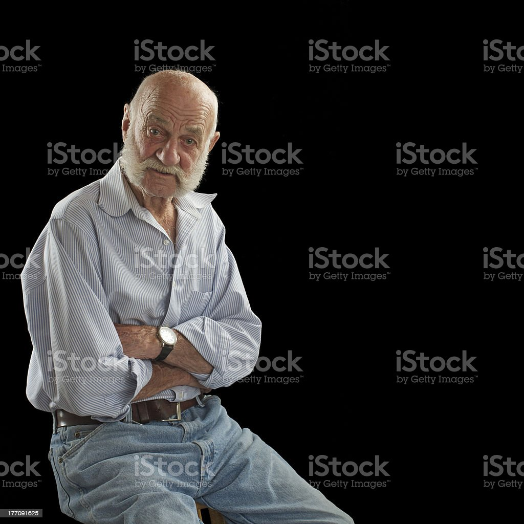 Elderly man crosses arms and looks interested stock photo