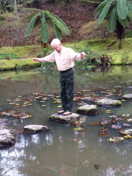 Elderly man demonstrating balance and vitality while walking across stones in a pond at the Terra Nostra Botanical Park on the island of Sao Miguel, Azores, Portugal. stock photo