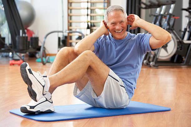 Alter Mann macht Sit-Ups im Fitnessstudio – Foto