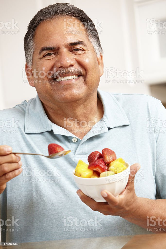 A elderly man eating a bowl of fruit stock photo