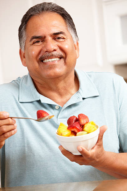 a elderly man eating a bowl of fruit - fat nutrient stock photos and pictures