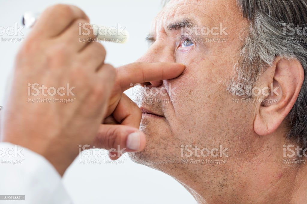 Elderly man examined by an ophthalmologist stock photo