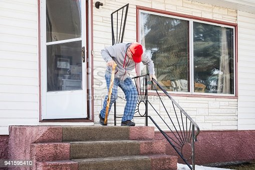 horizontal image of a caucasian elderly man exiting his home down the cement steps with a walking cane.