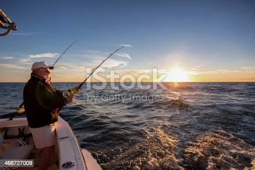 Man fishing on the ocean from the back of his boat at sunset