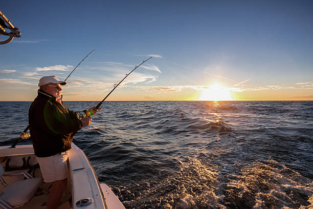 Elderly Man Fishing Man fishing on the ocean from the back of his boat at sunset fishing stock pictures, royalty-free photos & images